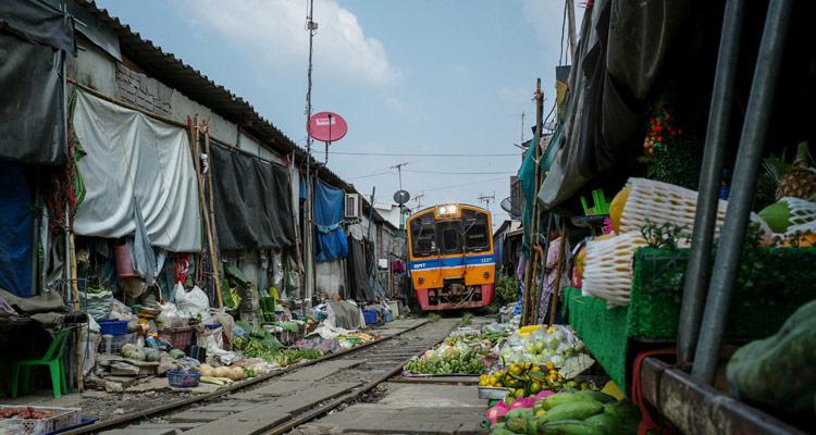 The train passes through market in Thailand